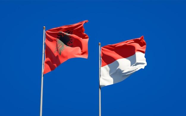 Belle bandiere di stato nazionali dell'indonesia e dell'albania insieme sul cielo blu