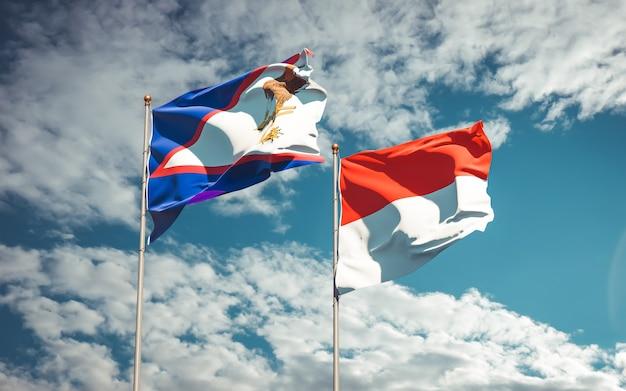 Belle bandiere nazionali dello stato dell'indonesia e samoa americane insieme sul cielo blu Foto Premium