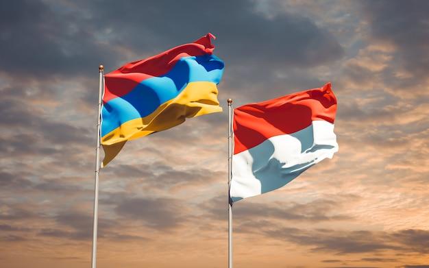 Belle bandiere nazionali di stato dell'indonesia e dell'armenia insieme sul cielo blu