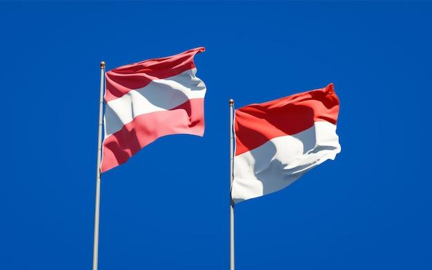 Belle bandiere di stato nazionali dell'indonesia e dell'austria insieme sul cielo blu