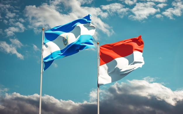 Belle bandiere di stato nazionali dell'indonesia e di el salvador insieme sul cielo blu