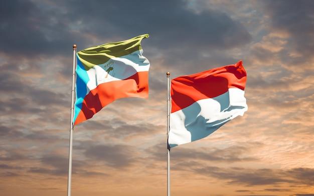 Belle bandiere di stato nazionali dell'indonesia e della guinea equatoriale insieme sul cielo blu