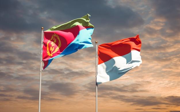Belle bandiere dello stato nazionale dell'indonesia e dell'eritrea insieme sul cielo blu