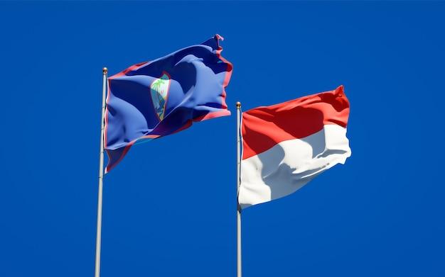 Belle bandiere nazionali di stato dell'indonesia e guam insieme sul cielo blu