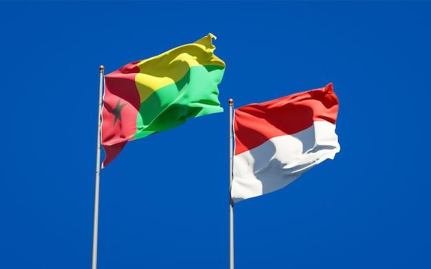 Belle bandiere nazionali dello stato dell'indonesia e della guinea-bissau insieme sul cielo blu