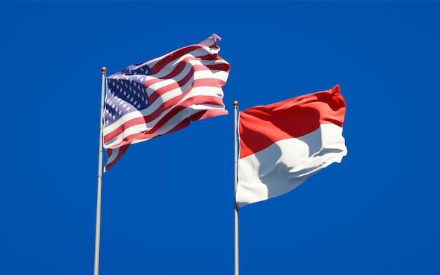Belle bandiere di stato nazionali dell'indonesia e degli stati uniti insieme sul cielo blu