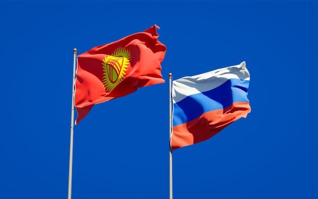 Belle bandiere di stato nazionali del kirghizistan e della russia insieme sul cielo blu. grafica 3d