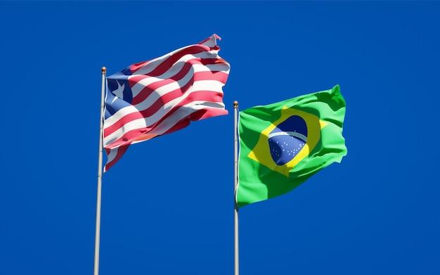 Belle bandiere di stato nazionali della liberia e del brasile insieme sul cielo blu