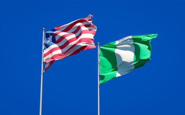 Belle bandiere di stato nazionali della liberia e della nigeria insieme sul cielo blu