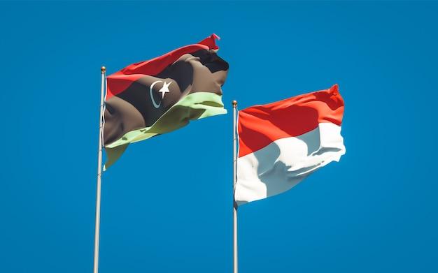 Belle bandiere dello stato nazionale della libia e dell'indonesia insieme sul cielo blu