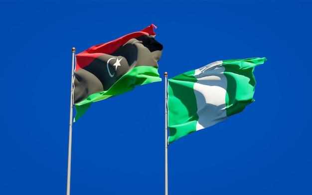 Belle bandiere di stato nazionali della libia e della nigeria insieme sul cielo blu