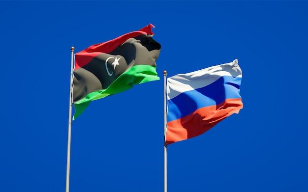 Belle bandiere di stato nazionali della libia e della russia insieme sul cielo blu. grafica 3d