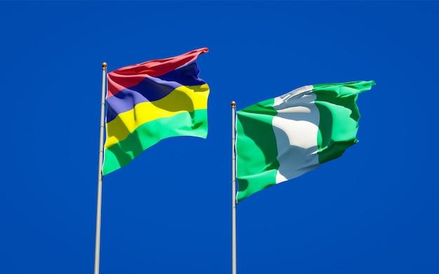 Belle bandiere di stato nazionali di mauritius e nigeria insieme sul cielo blu