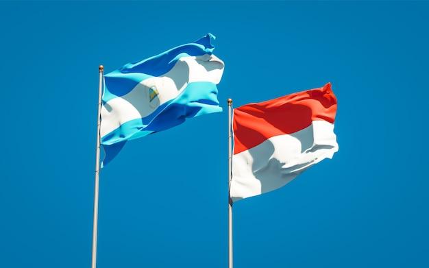 Belle bandiere nazionali dello stato del nicaragua e dell'indonesia insieme sul cielo blu