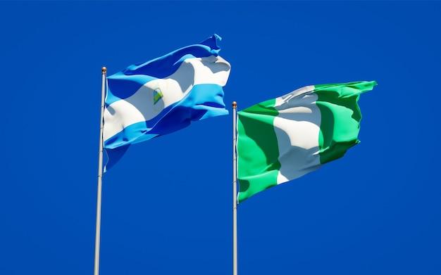 Belle bandiere di stato nazionali del nicaragua e della nigeria insieme sul cielo blu