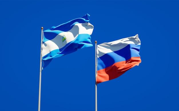 Belle bandiere di stato nazionali del nicaragua e della russia insieme sul cielo blu. grafica 3d