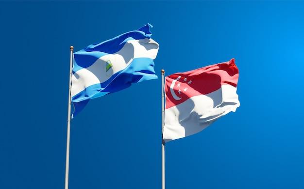 Belle bandiere nazionali dello stato del nicaragua e singapore insieme