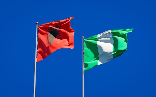 Belle bandiere di stato nazionali della nigeria e dell'albania insieme sul cielo blu