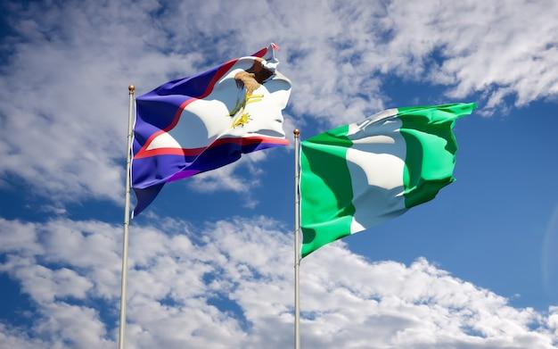 Belle bandiere dello stato nazionale della nigeria e delle samoa americane insieme sul cielo blu Foto Premium