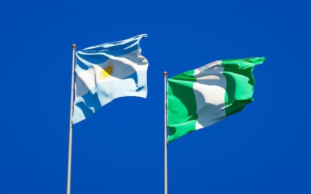 Belle bandiere di stato nazionali della nigeria e dell'argentina insieme sul cielo blu
