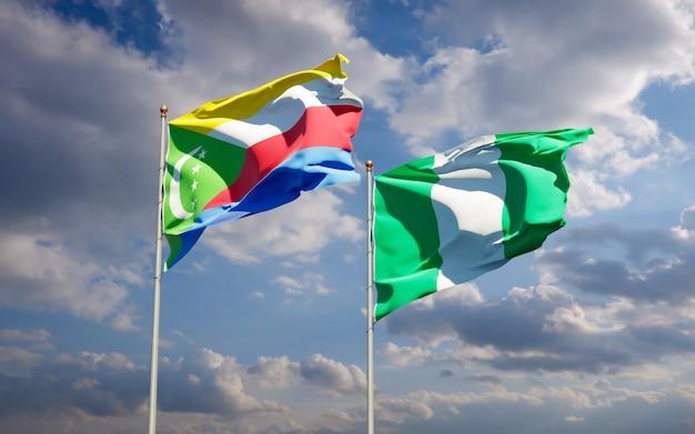 Belle bandiere nazionali dello stato della nigeria e delle comore insieme sul cielo blu