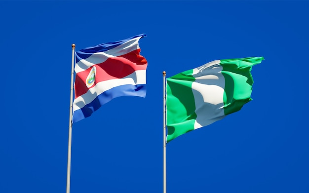 Belle bandiere di stato nazionali della nigeria e della costa rica insieme sul cielo blu