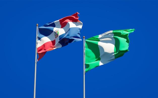 Belle bandiere di stato nazionali della nigeria e della repubblica dominicana insieme sul cielo blu