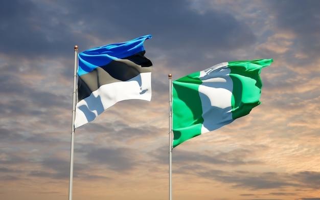 Belle bandiere di stato nazionali della nigeria e dell'estonia insieme sul cielo blu