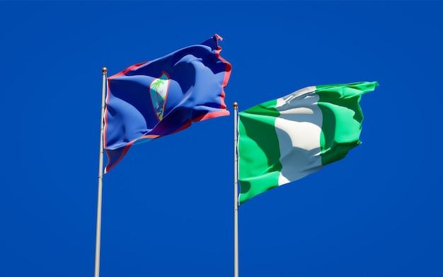 Belle bandiere di stato nazionali della nigeria e guam insieme sul cielo blu