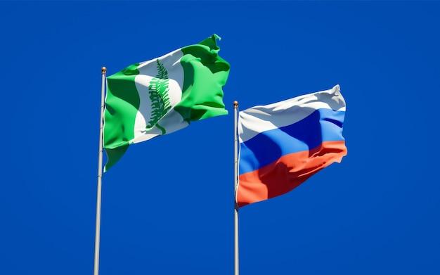 Belle bandiere nazionali dello stato dell'isola di norfolk e della russia insieme sul cielo blu. grafica 3d