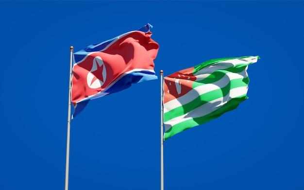 Belle bandiere di stato nazionali della corea del nord e dell'abkhazia insieme