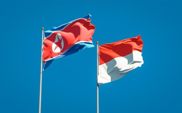 Belle bandiere di stato nazionali della corea del nord e dell'indonesia insieme sul cielo blu