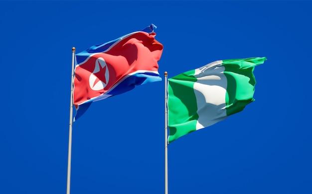 Belle bandiere di stato nazionali della corea del nord e della nigeria insieme sul cielo blu