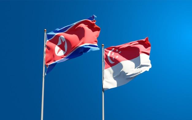Belle bandiere di stato nazionali della corea del nord e singapore insieme