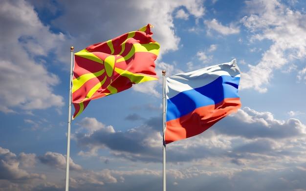 Belle bandiere di stato nazionali della macedonia del nord e della russia insieme sul cielo blu. grafica 3d