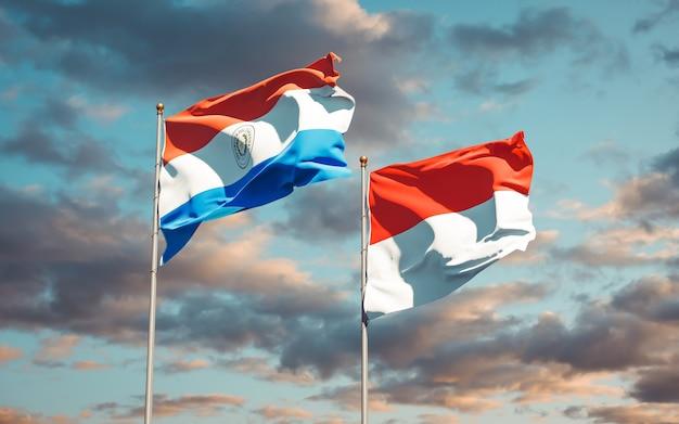 Belle bandiere nazionali dello stato del paraguay e indonesia insieme sul cielo blu