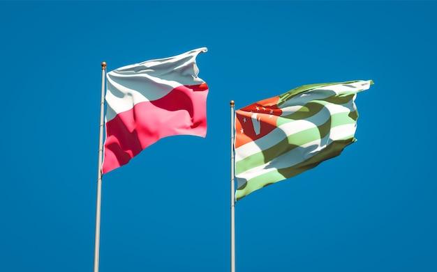Belle bandiere dello stato nazionale della polonia e dell'abkhazia insieme sul cielo blu. grafica 3d