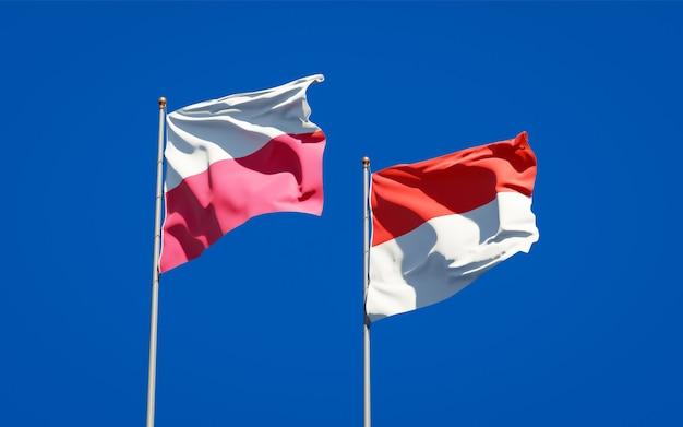 Belle bandiere di stato nazionali della polonia e dell'indonesia insieme sul cielo blu