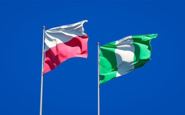 Belle bandiere di stato nazionali della polonia e della nigeria insieme sul cielo blu