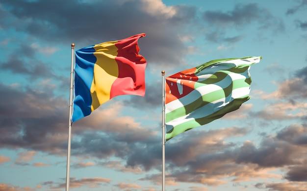 Belle bandiere di stato nazionale della romania e dell'abkhazia insieme sul cielo blu. grafica 3d