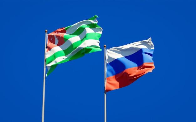Belle bandiere nazionali dello stato della russia e dell'abkhazia insieme sul cielo blu. grafica 3d