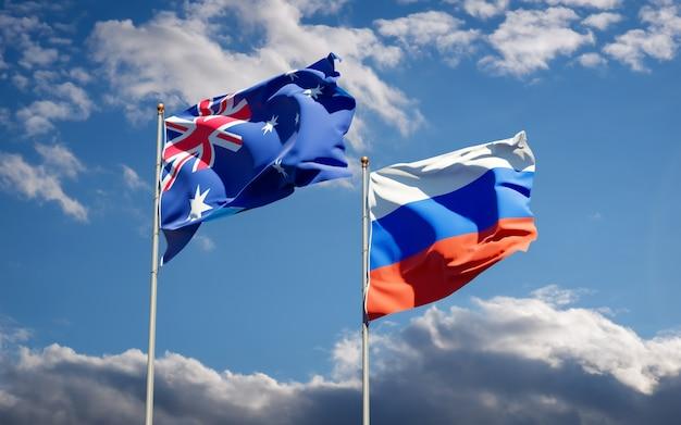 Belle bandiere di stato nazionali della russia e dell'australia insieme sul cielo blu. grafica 3d