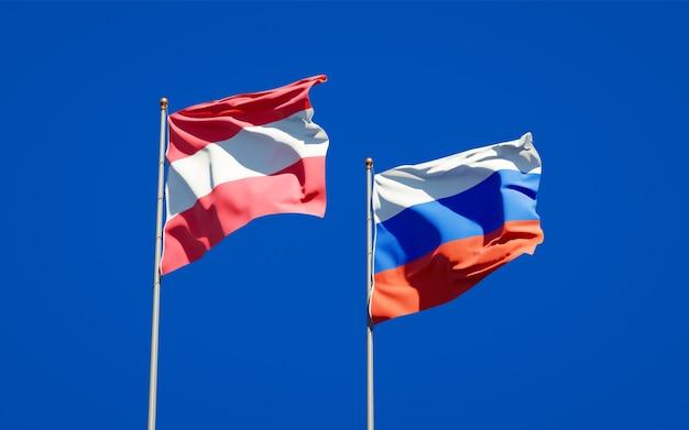 Belle bandiere di stato nazionali della russia e dell'austria insieme sul cielo blu. grafica 3d
