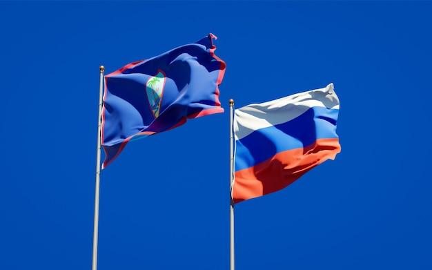 Belle bandiere nazionali di stato della russia e guam insieme sul cielo blu. grafica 3d