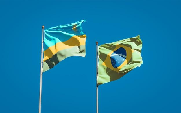 Belle bandiere nazionali dello stato del ruanda e del brasile insieme sul cielo blu