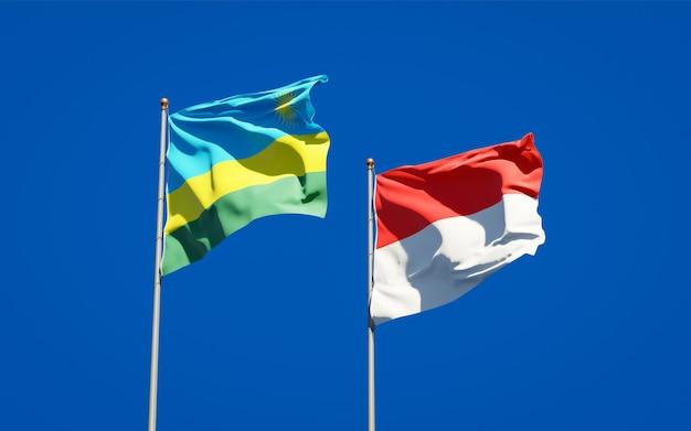 Belle bandiere di stato nazionali del ruanda e dell'indonesia insieme sul cielo blu