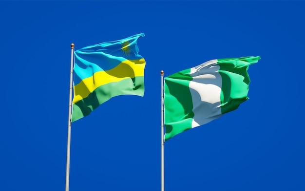 Belle bandiere di stato nazionali del ruanda e della nigeria insieme sul cielo blu