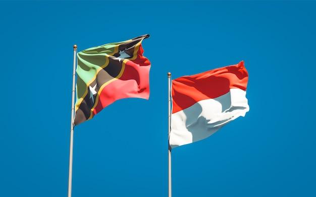 Belle bandiere dello stato nazionale di saint kitts e nevis e indonesia insieme sul cielo blu