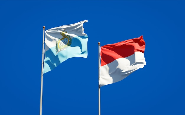 Belle bandiere nazionali dello stato di san marino e indonesia insieme sul cielo blu
