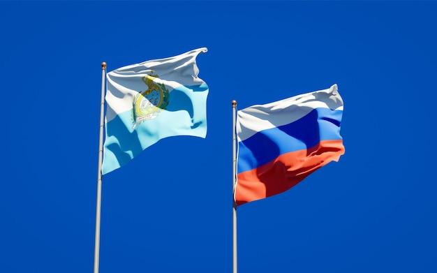 Belle bandiere nazionali dello stato di san marino e russia insieme sul cielo blu. grafica 3d